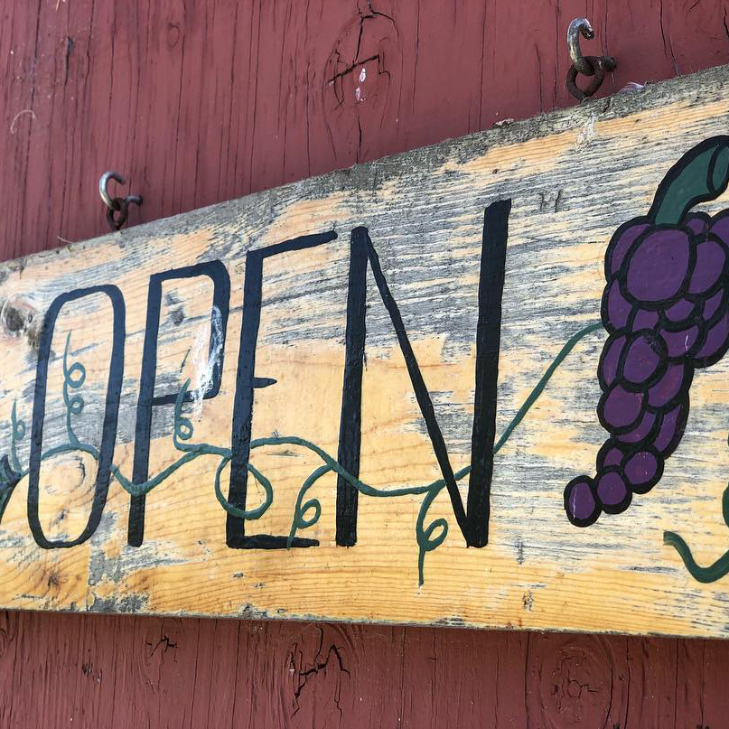 Battaglini winery's Open sign hanging on the outside door of their red barn tasting room